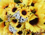 Сватбен букет от слънчогледи, аранжиран с перли, декоративна зеленина и обгърнат от разкошен тюл